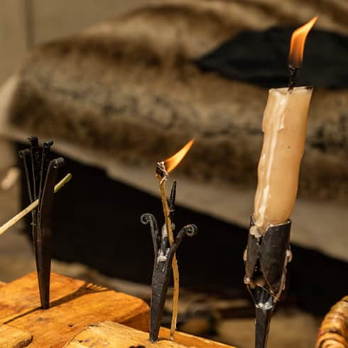 The image shows the heat and flame of a beeswax candle (right) and some rushlights erected in an iron pricket (left)