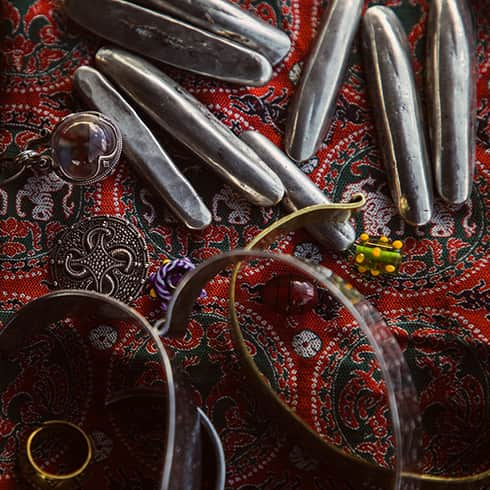 The image shows silver and bronze jewellery on a patterned silk background.