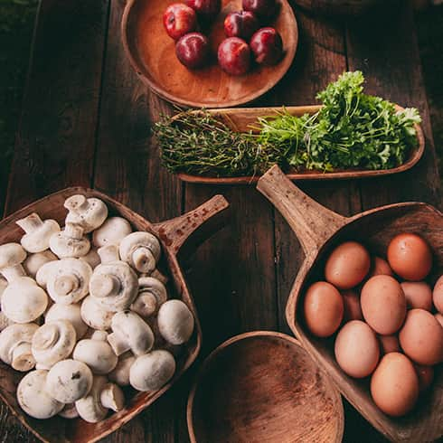 The image shows various food stuff ready for cooking. Eggs, Mushrooms, herbs and fruit.