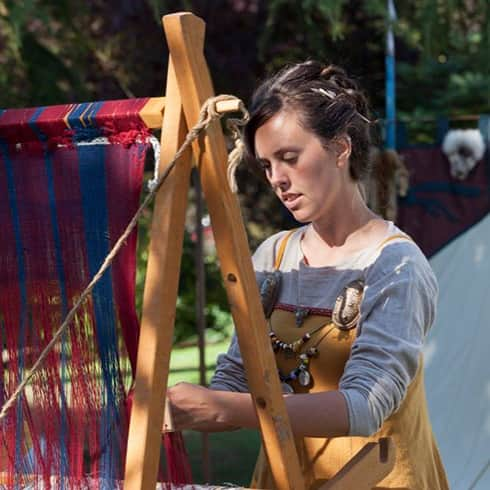 The image shows a woman weaving woollen fabric on a warp-weighted loom.