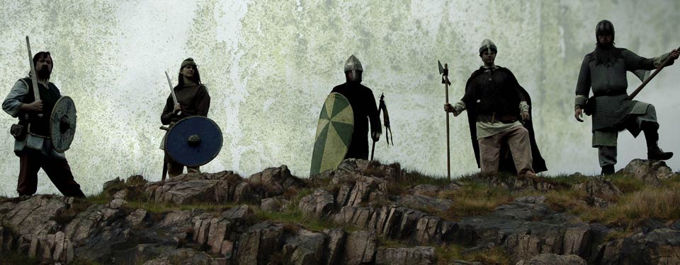 Image shows a group of Vikings almost in silhouette at the top of a cliff face.