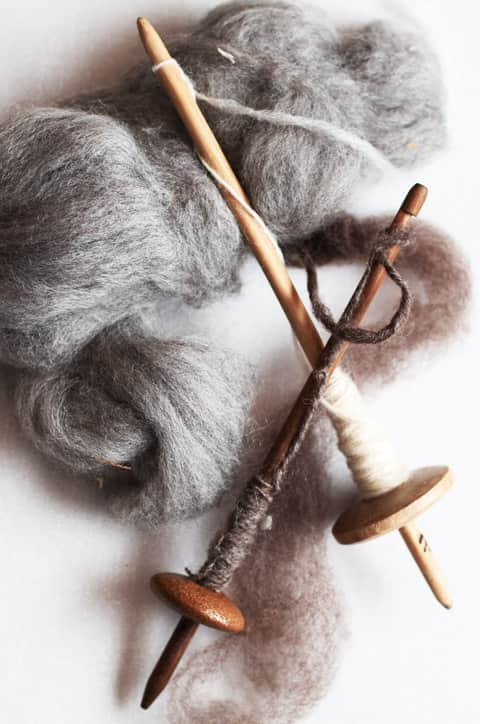 A pair of spindle whorls with fleece ready to be spun into wool.